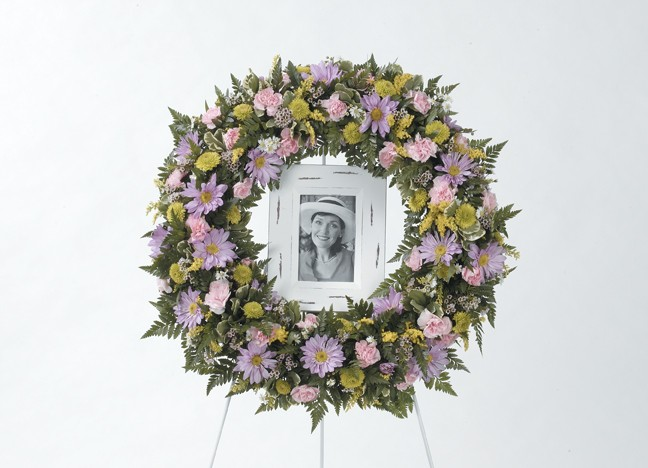 Large round memorial wreath around a picture